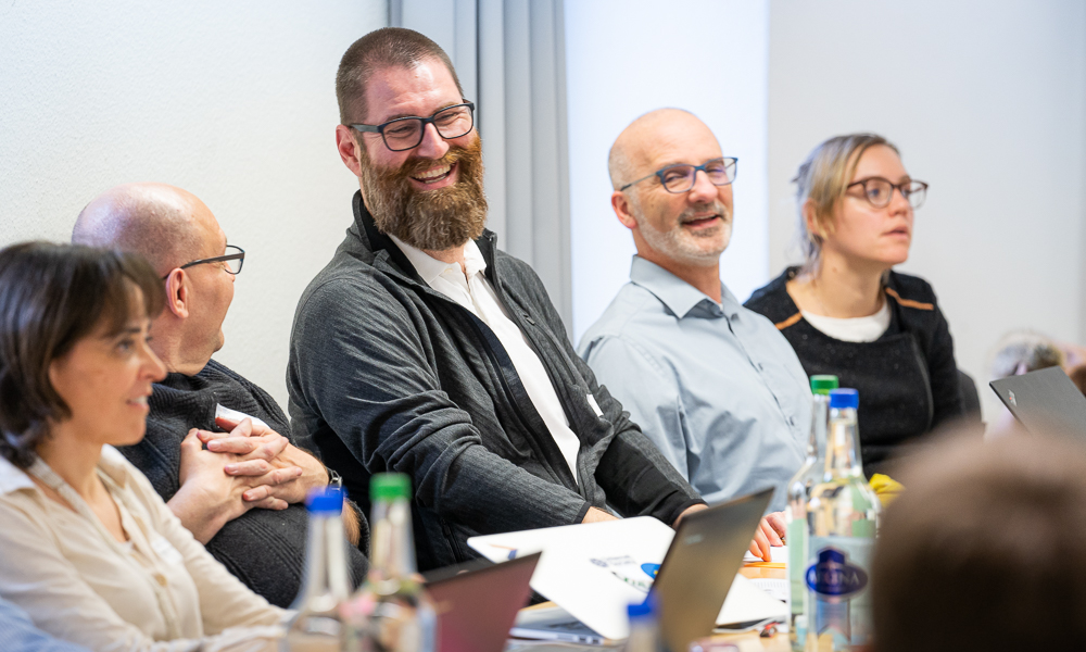 Partners talking and laughing at the connectome pilot kick-off